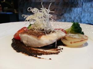 鱸のポワレ ミニオニオンのポシェと共に イカ墨オリーブのソースで